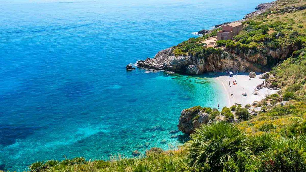 La spiaggia paradisiaca in Italia: perfetta acqua turchese trasparente, ciottoli bianchi circondati dal verde. Cala denominata «Cala Tonnarella dell'Uzzo», Riserva naturale «dello Zingaro», San Vito lo Capo, Sicilia