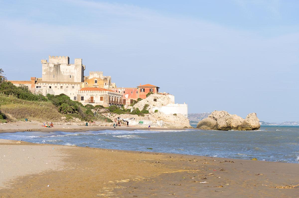 Il bellissimo castello di Falconara in Sicilia visto dalla spiaggia di sabbia. Era una soleggiata giornata estiva in questo bel posto nascosto situato vicino a Butera, Caltanissetta